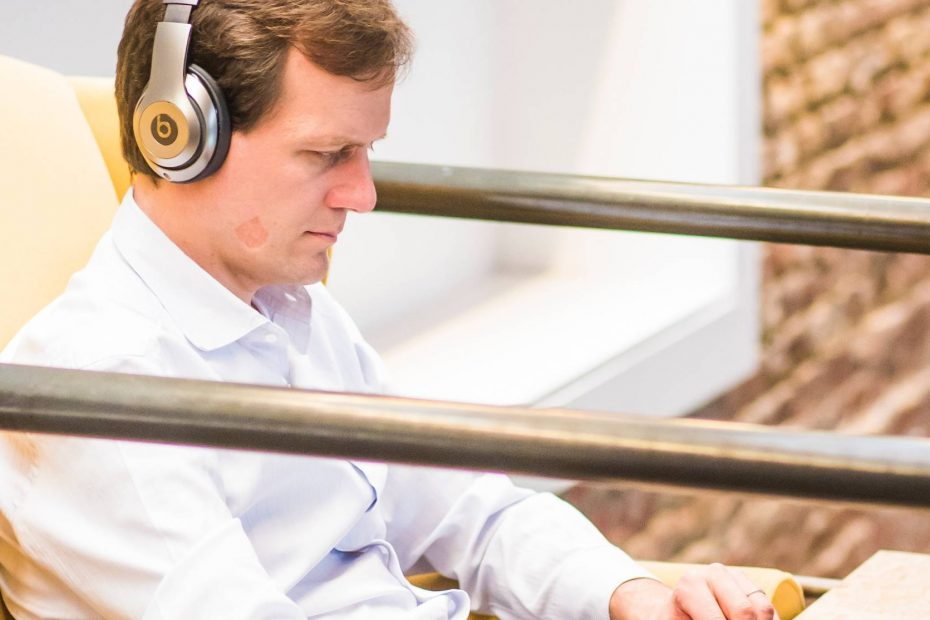 Man wearing headphones typing on the laptop