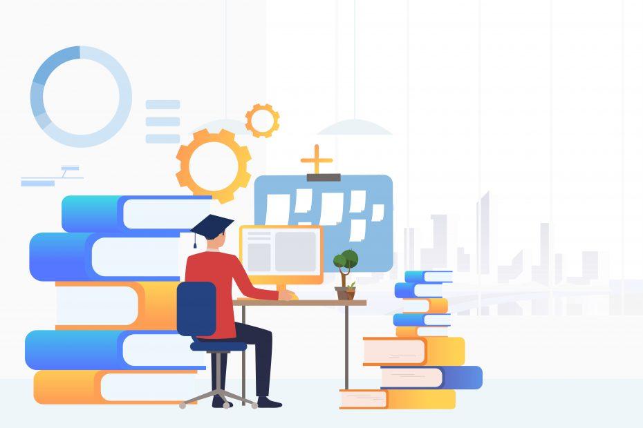 Student in graduation cap using computer at desk