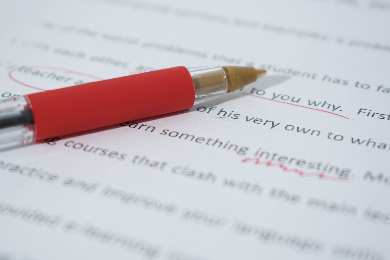 a close up image of a paper being proofread using a red pen